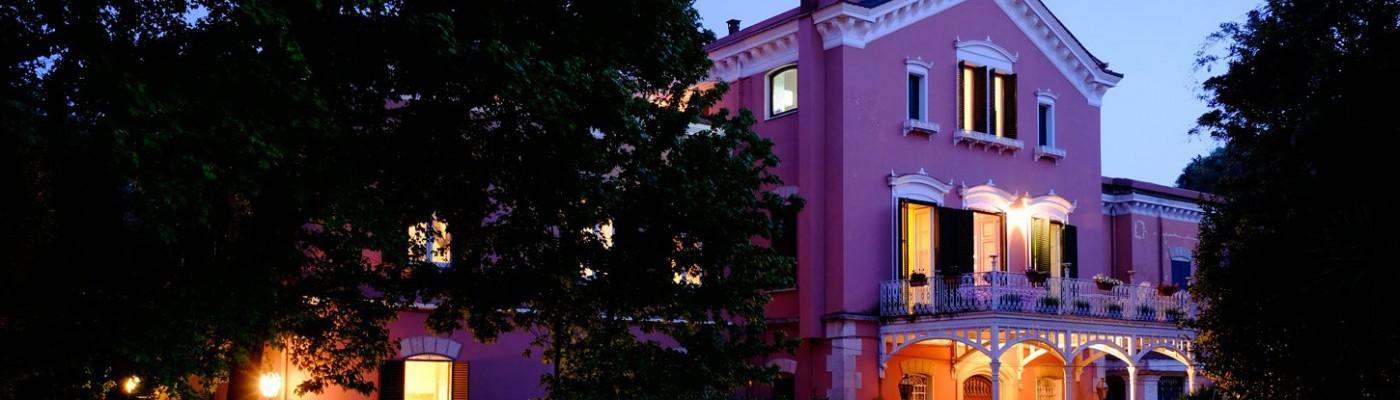Facciata della villa, tagliata, con luci accese ma cielo ancora azzurro